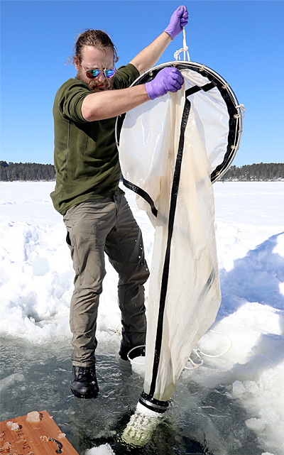 A UMN Duluth assistant professor pulls a net full of zooplankton from a frozen lake