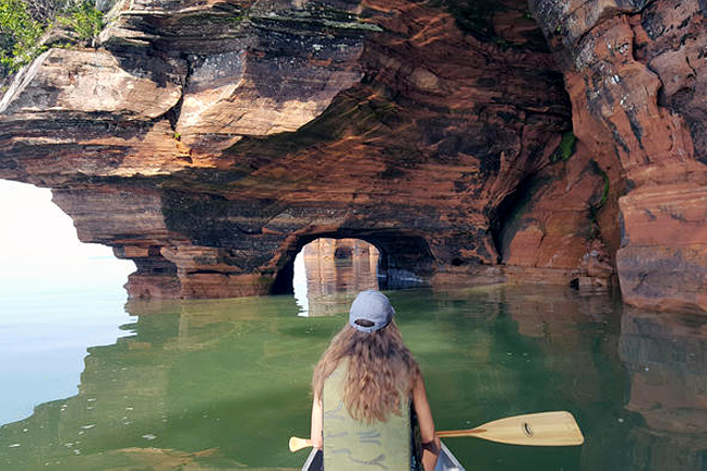 A woman paddles a canoe near a rock formation on Lake Superior
