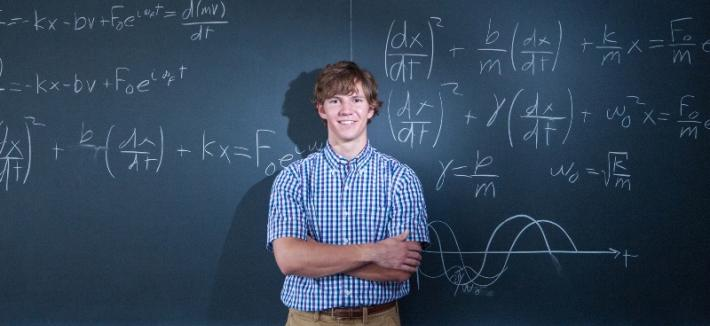 student infront of chalkboard with equations on the board