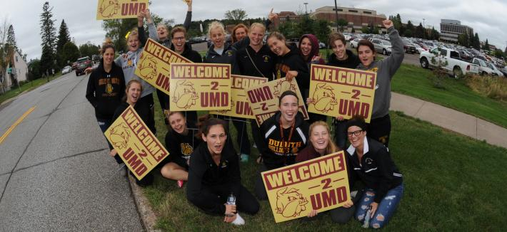 Students with Welcome Week Signs