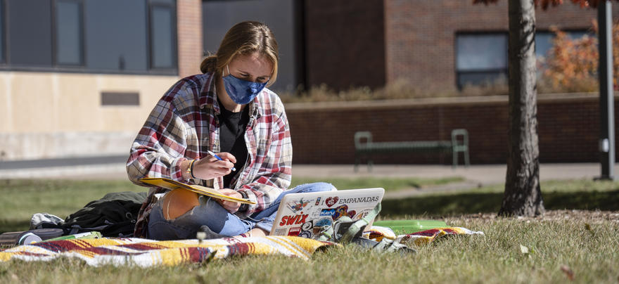 Student in mask studying outside on the UMD campus