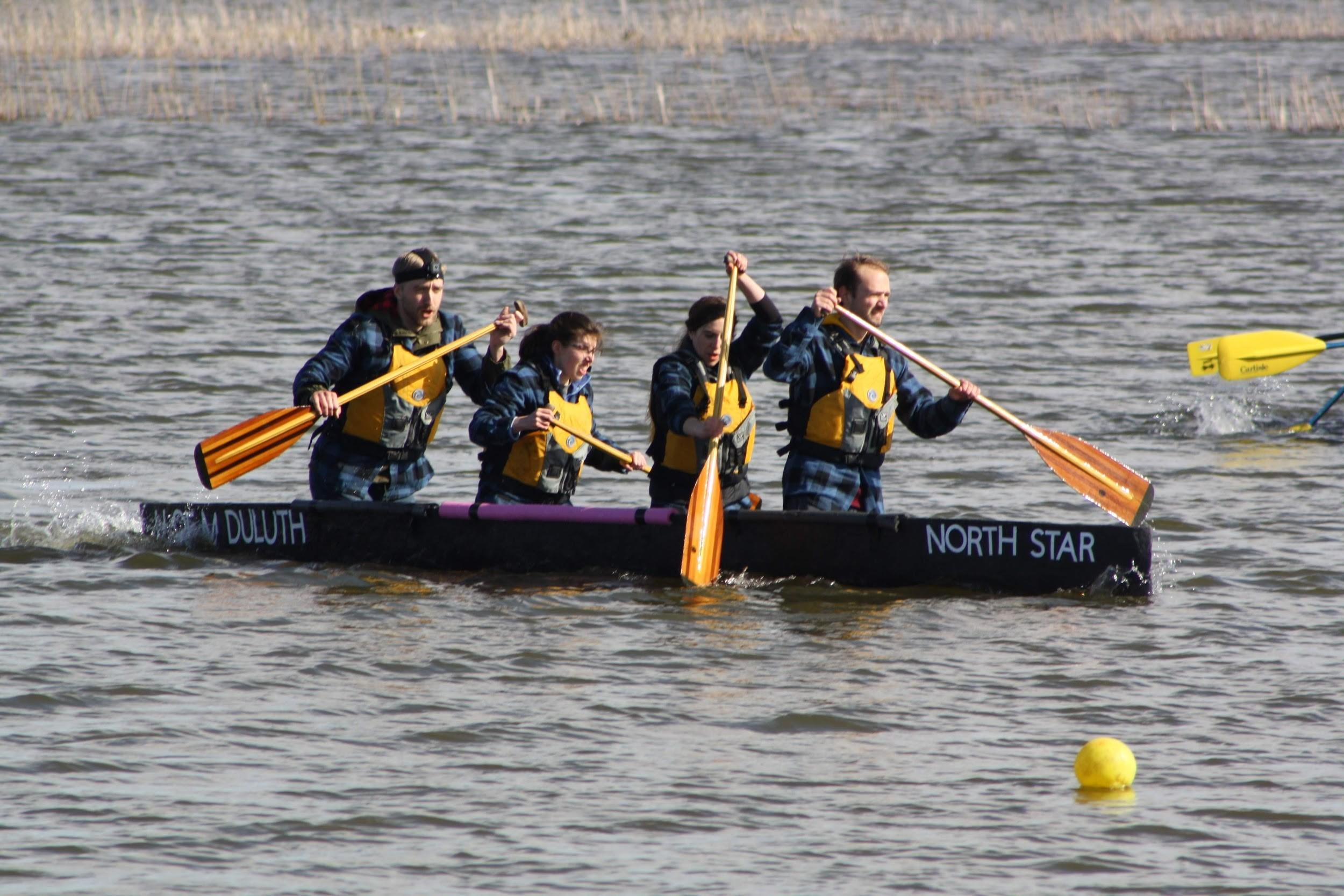 4 students rowing the concrete canoe that is floating in the water